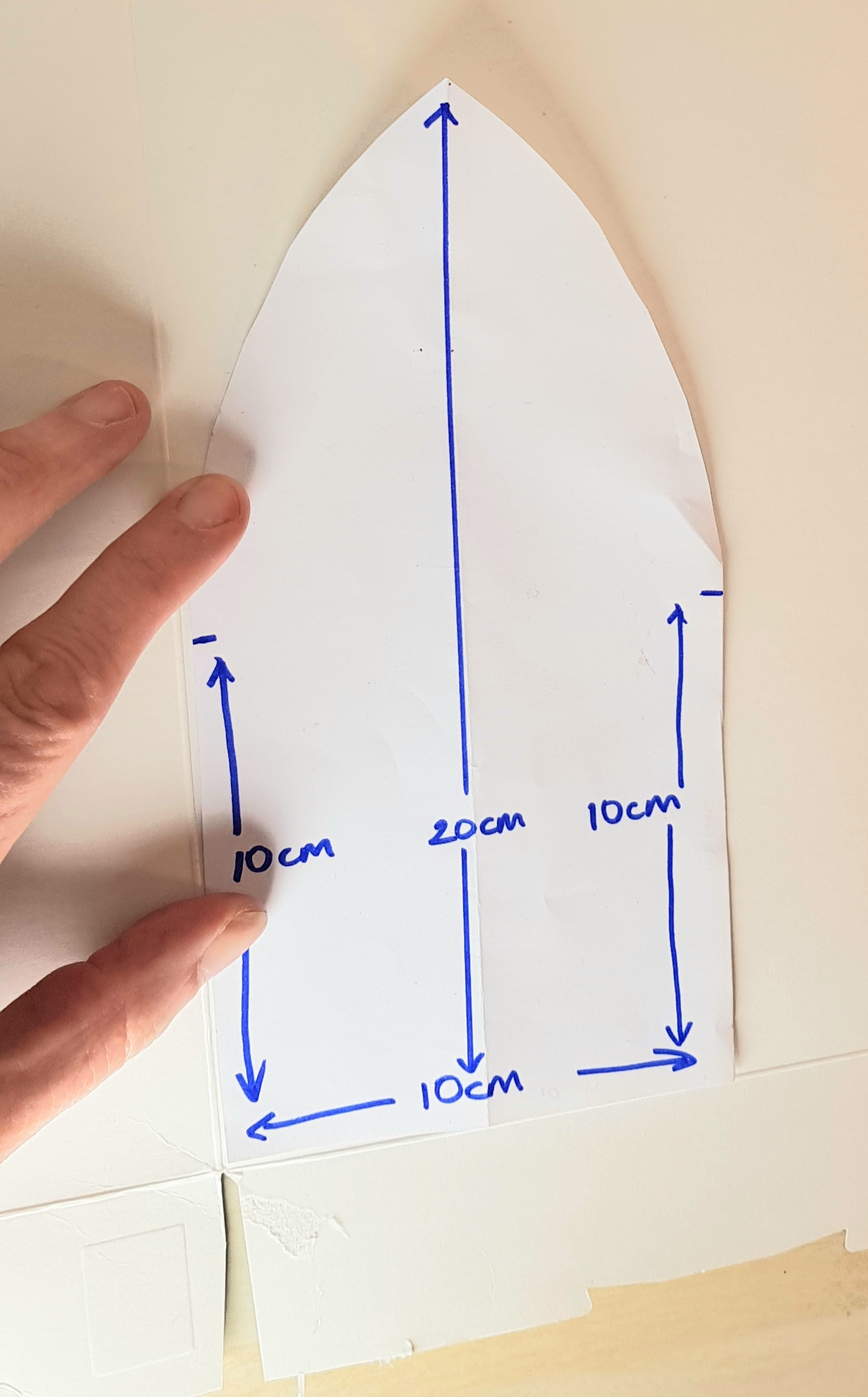 A template of a ship's shape is being used on cardboard to create a base for the craft. The template has measurements written on. 10cm across, 10cm of straight edges going up, and then curved edges to create a full height of 20cm.