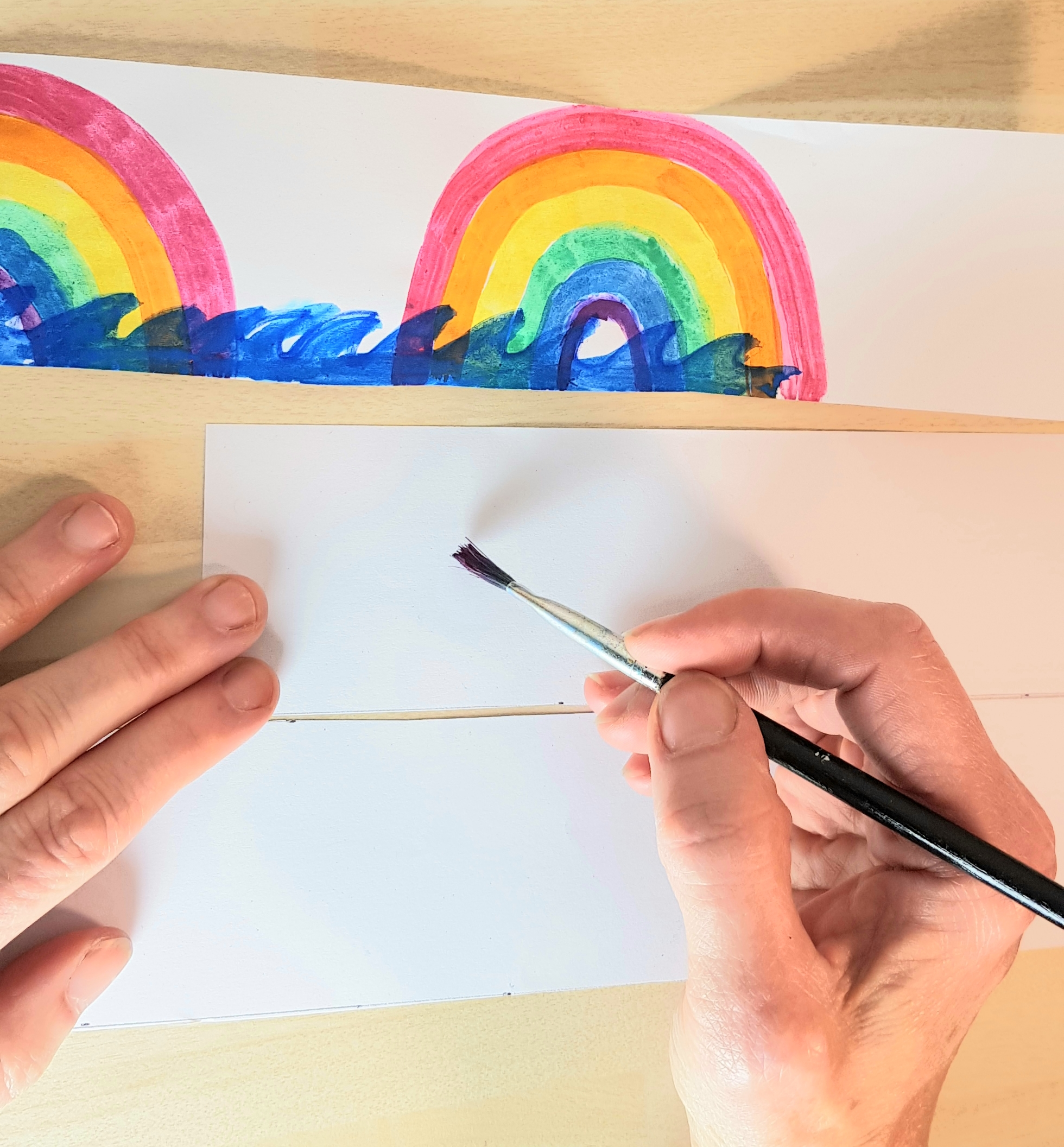 3 strips of paper have been cut out. One is decorated with rainbows and the ocean. Someone is preparing to start decorating the second strip of paper with a paintbrush.