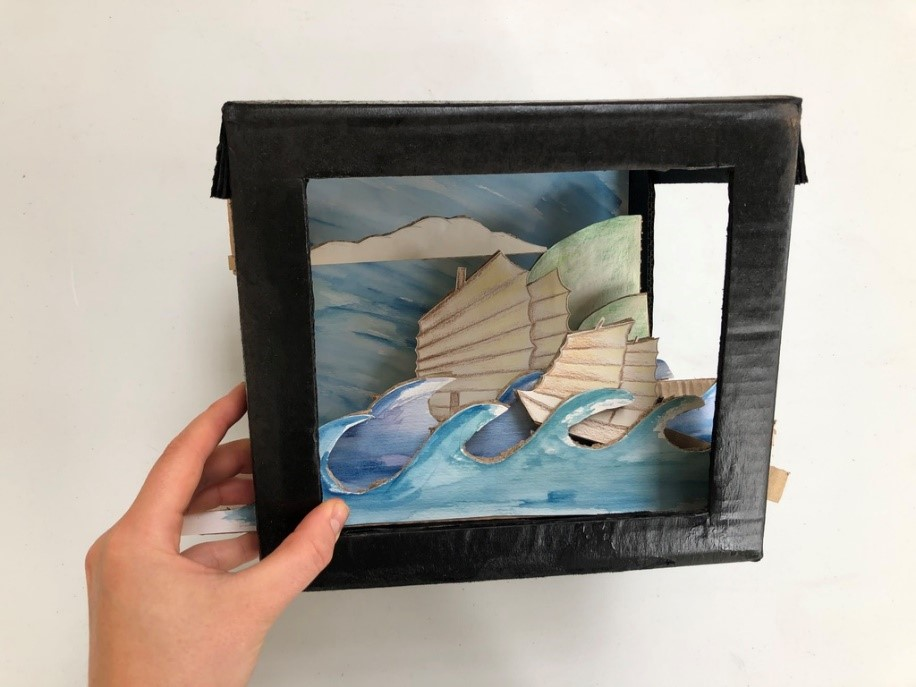 A scene has been created of a ship behind waves, inside a cardboard box.