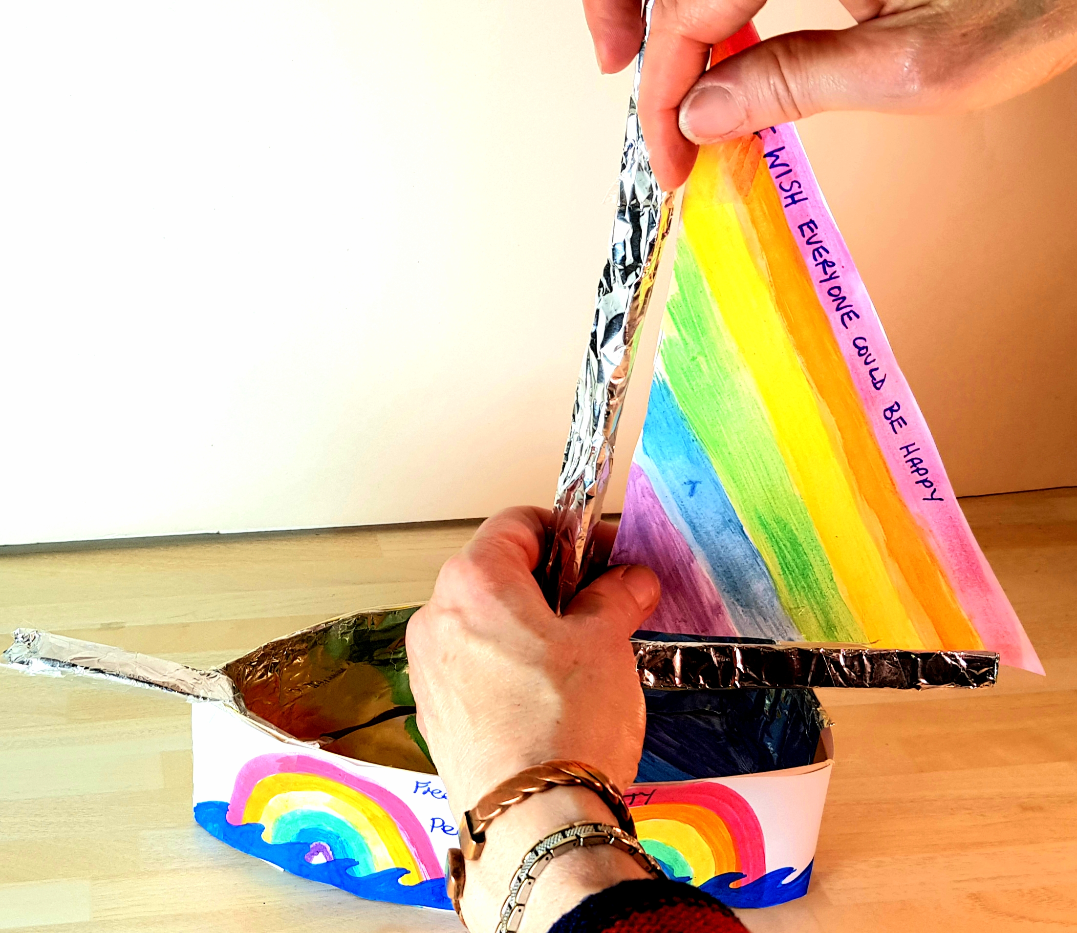 A ship has been made out of card and decorated with rainbow colours. Someone is adding a sail with rainbow stripes to the mast.