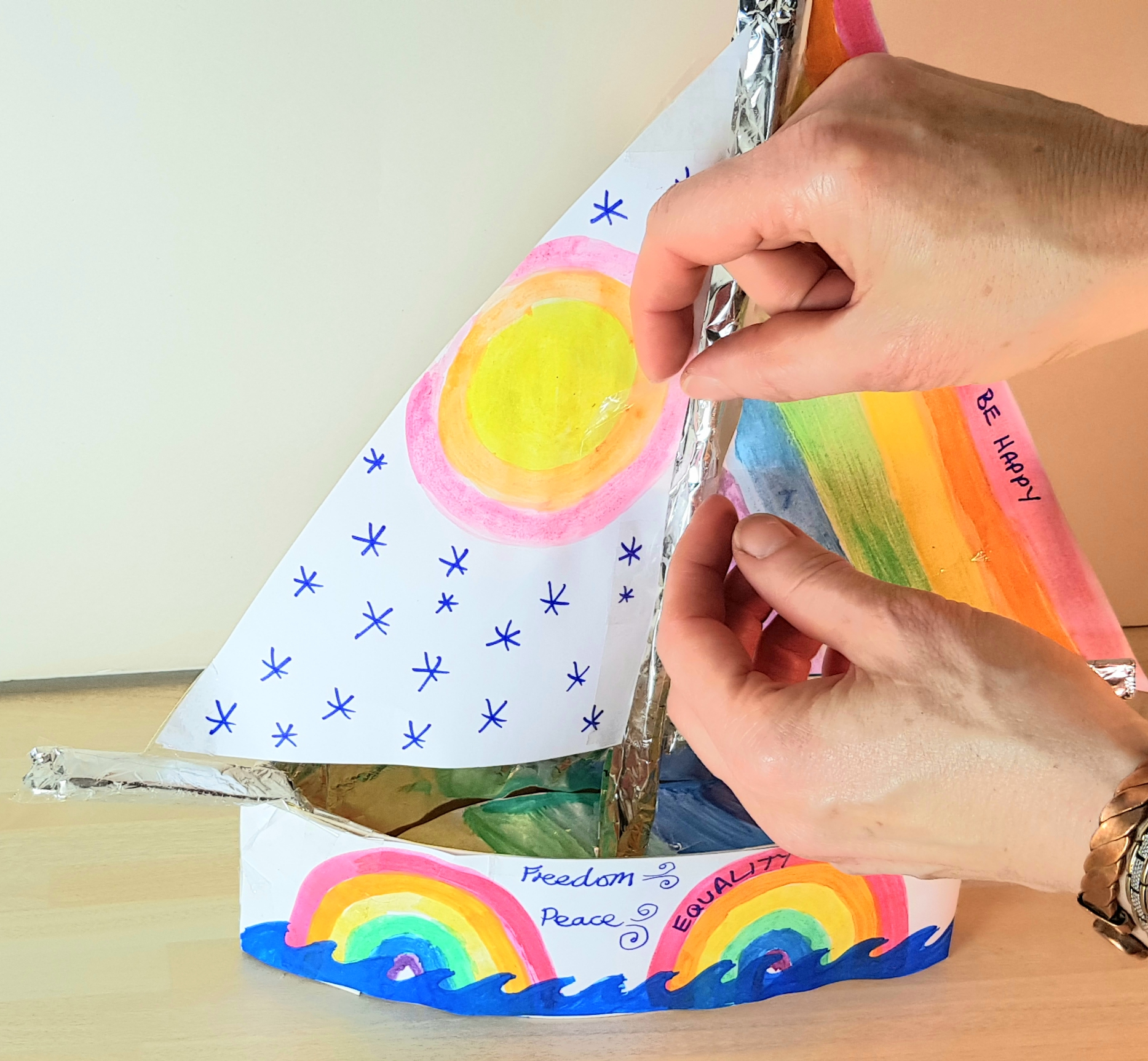 A ship has been made out of card and decorated with rainbow colours. Someone is adding a second sail with stars and a yellow sun to the mast.
