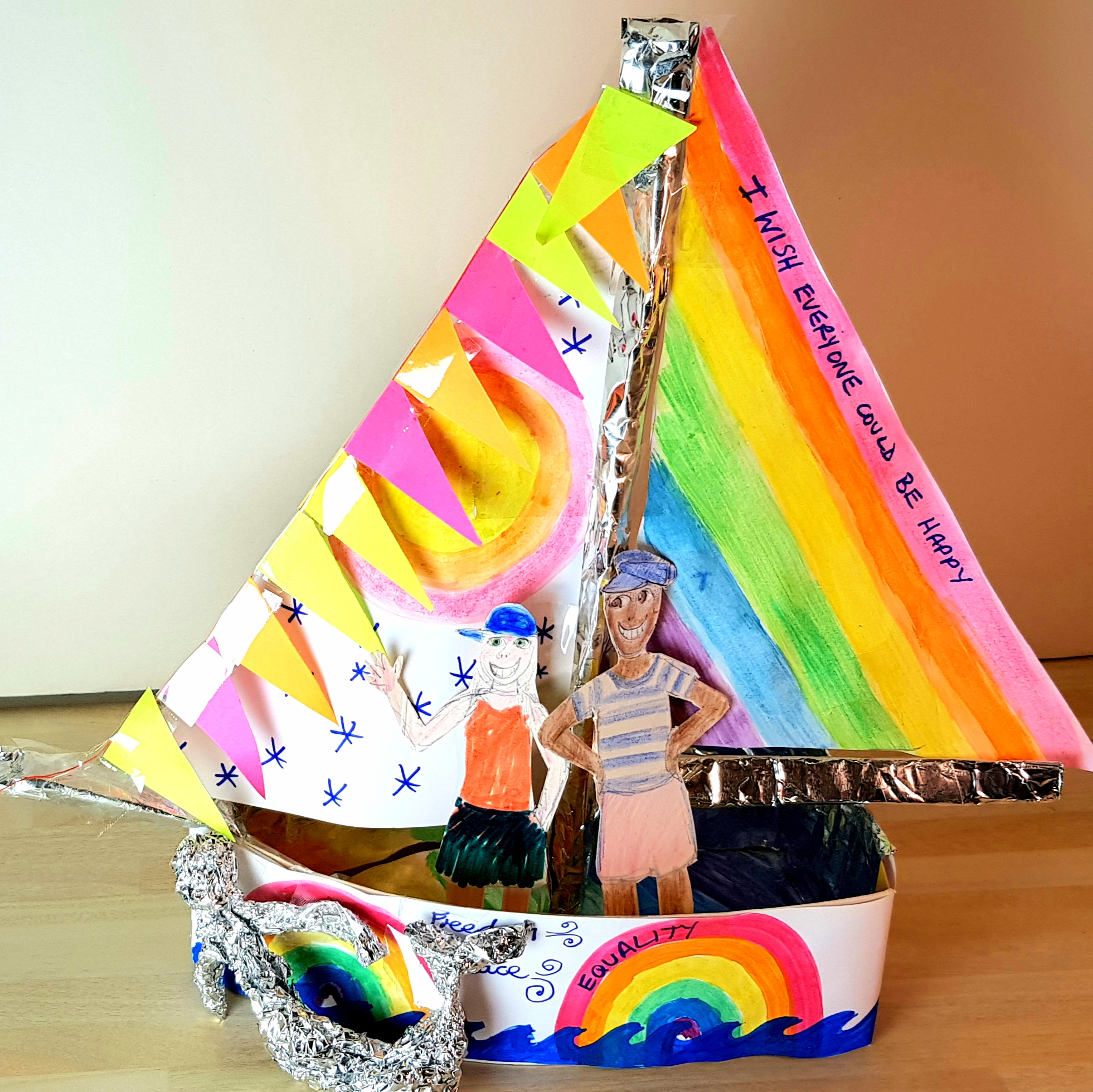 A ship has been made out of paper and tinfoil, decorated with rainbow colours.