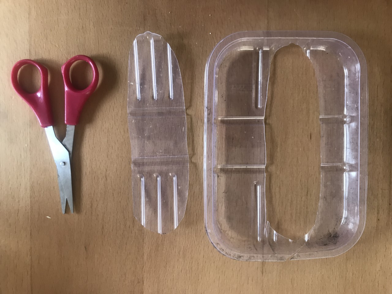 Image shows a pair of red scissors next to a recycled plastic tray. An oval shape has been cut out of the centre.