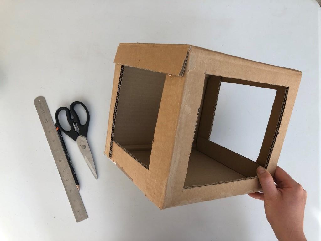 A cardboard box has three large sqaures cut into three sides, creating windows.