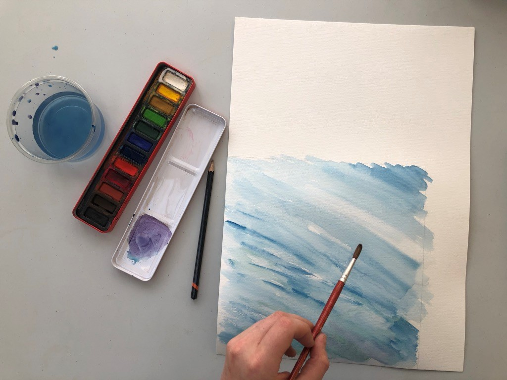 Someone decorates a piece of white paper with blue watercolours. The paints, paintbrushes and water in a pot sit nearby.