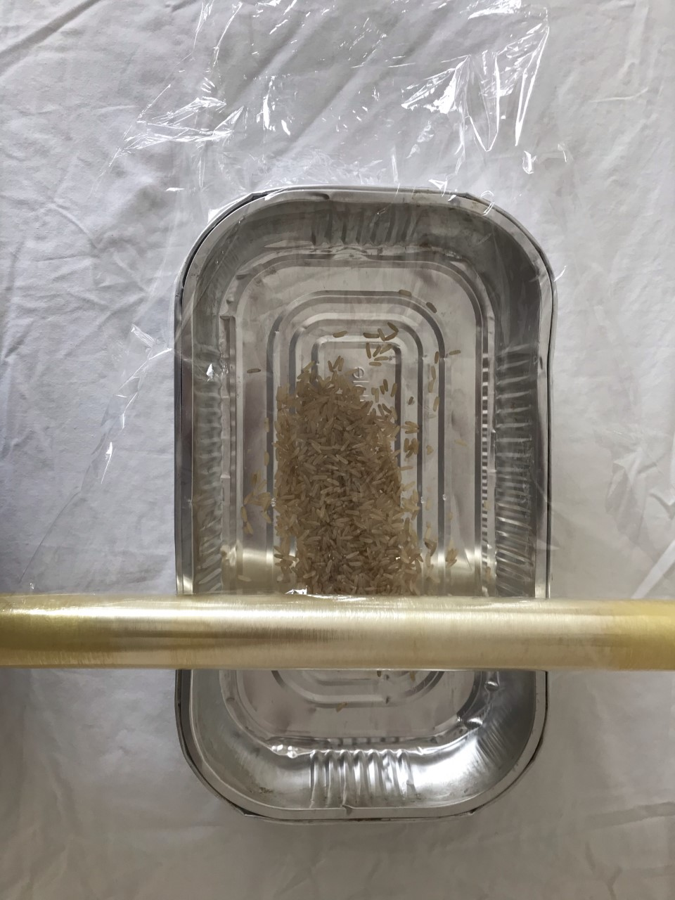 A metal tray with rice inside. Cellophane is being measured out to cover the top of the tray.