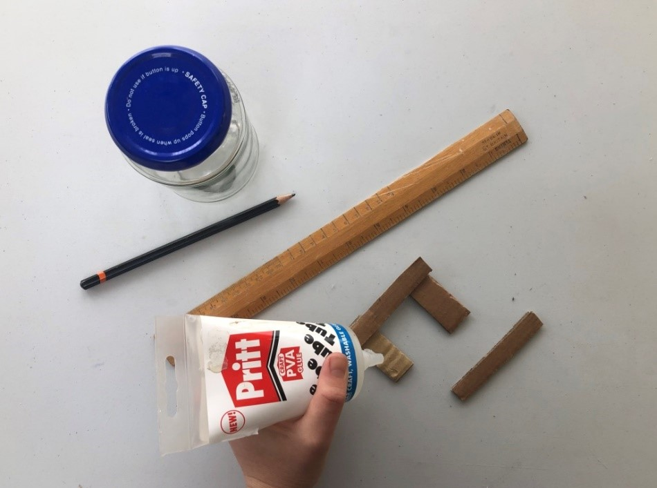 Using glue someone sticks two long and short pieces of cardboard together to form a rectangle shaped stand.