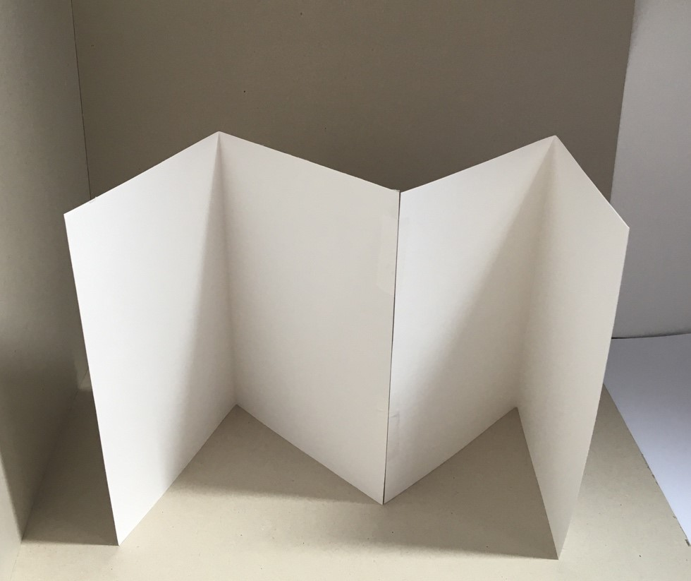 Two pieces of white paper, with a fold crease on each, are stuck together with tape.
