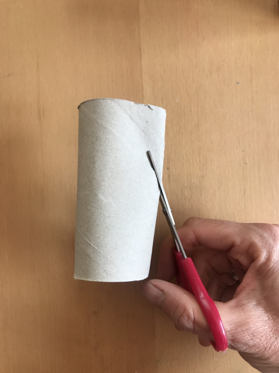 A person cuts into a loo roll tube with a pair of red scissors