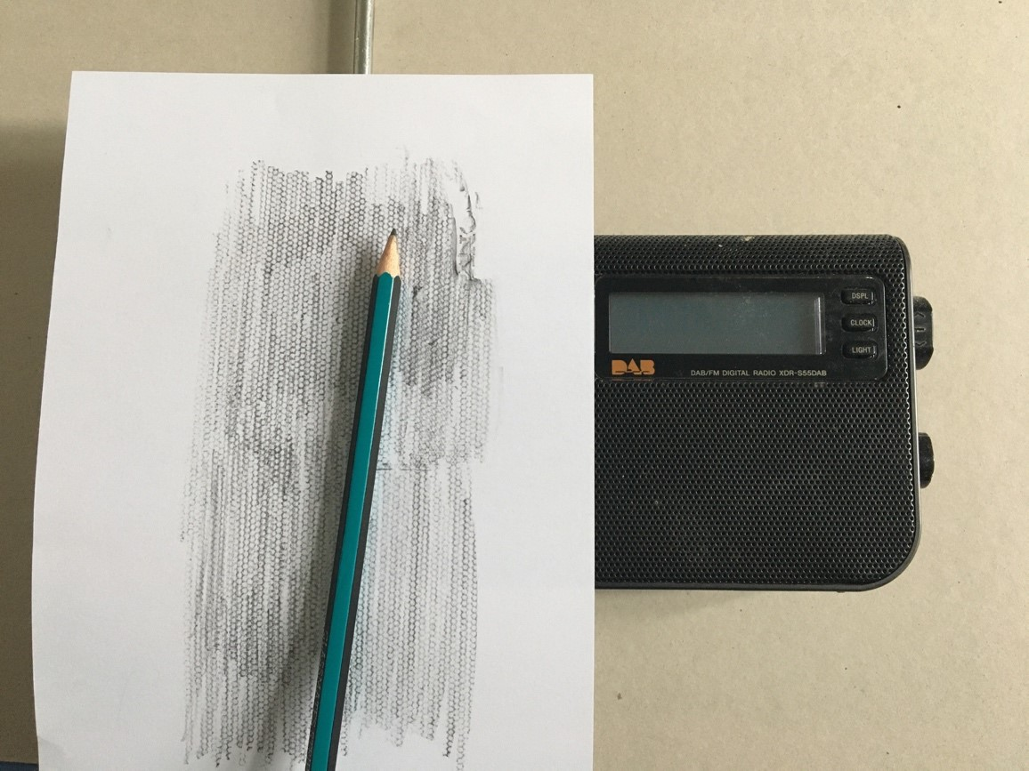 A piece of white paper is on top of a radio. A pencil sits on top showing that a rubbing has been taken of the pattern on the radio.