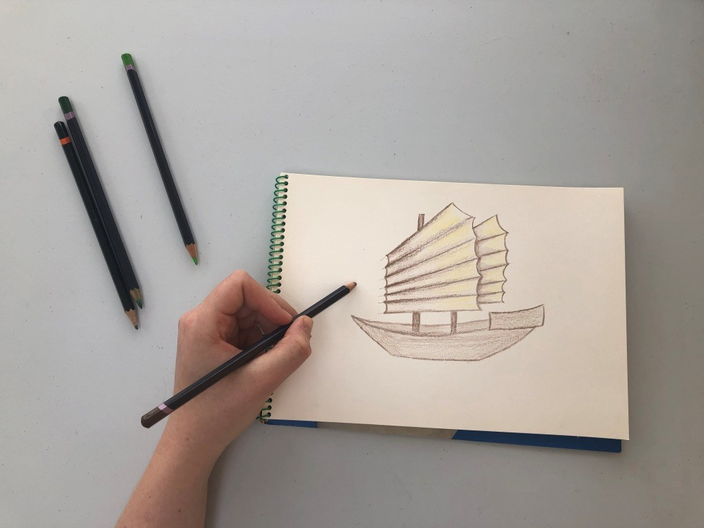 A drawing of a Junk in a sketchbook. Coloured pencils lie nearby