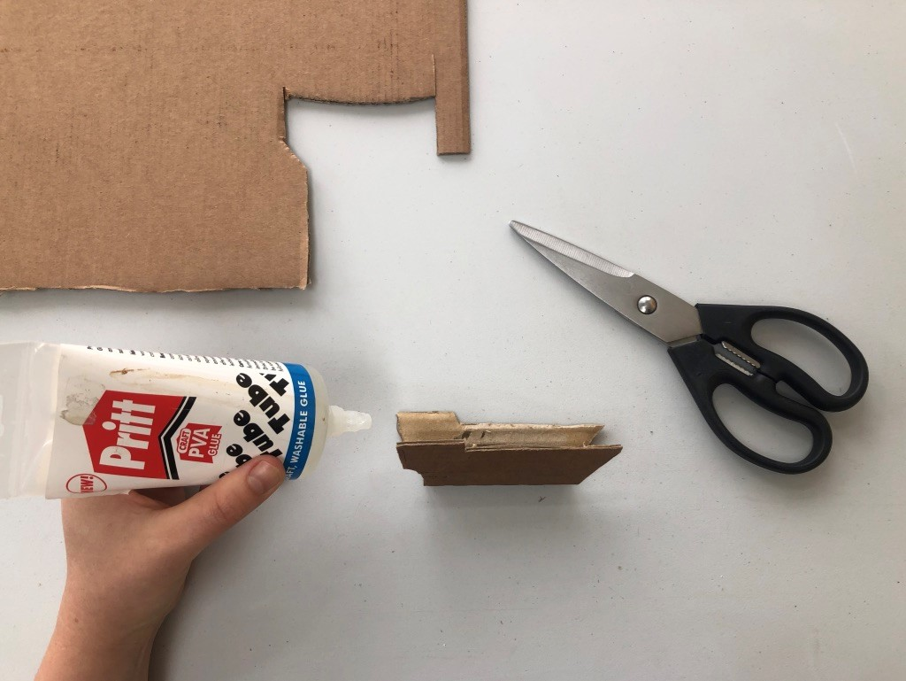 A small ship's hull has been cut out of some cardboard and is being glued together.