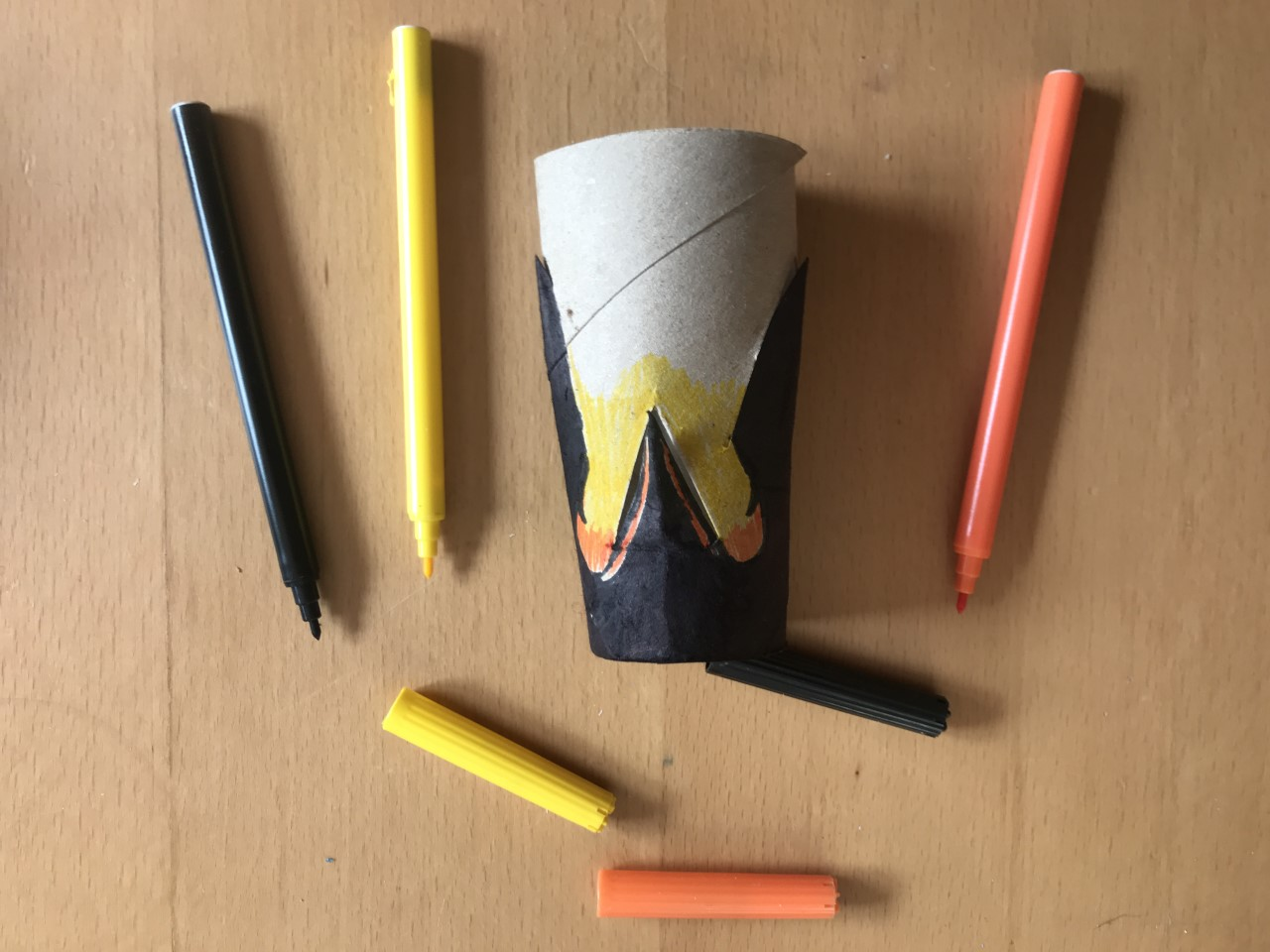 Three felt tip pens, orange, yellow and black, lie next to a tube coloured to look like a penguin