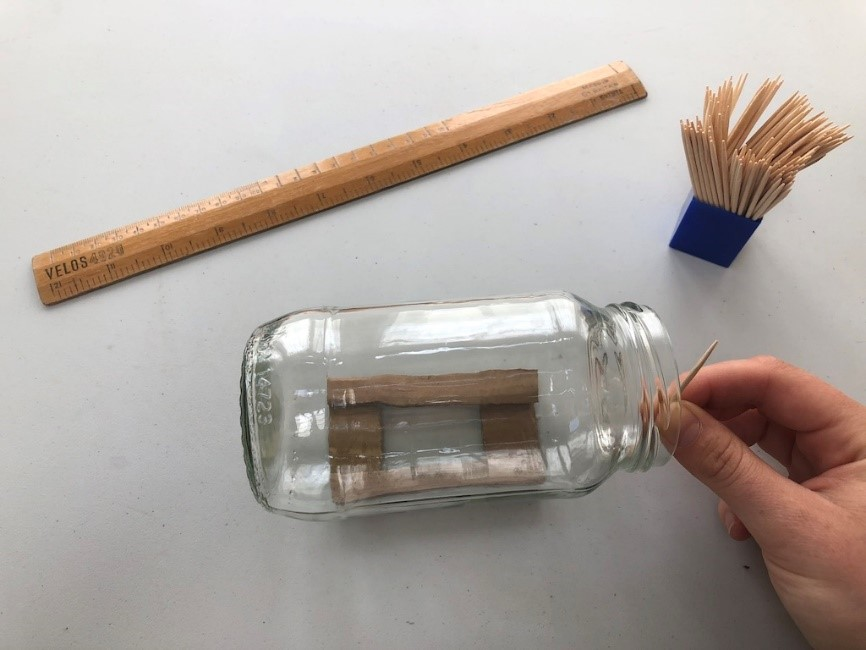 An empty jar lies on it's side on top of a stand made of cardboard. Someone hold a toothpick beside the jar to measure it's height.