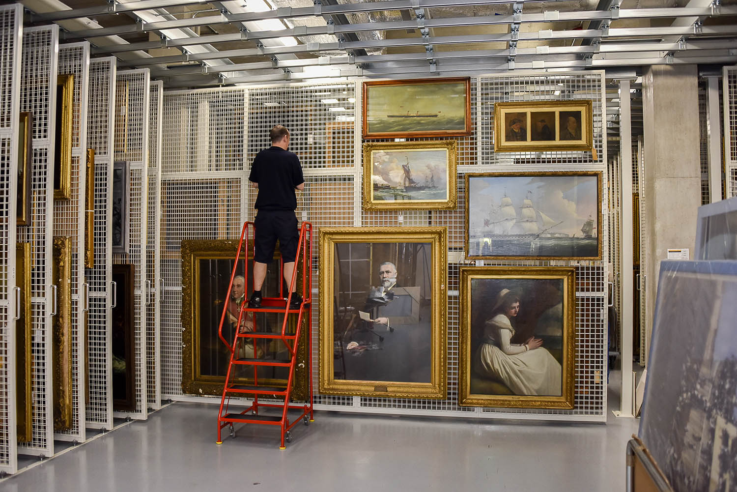 Image of Constantine technician hanging small paintings