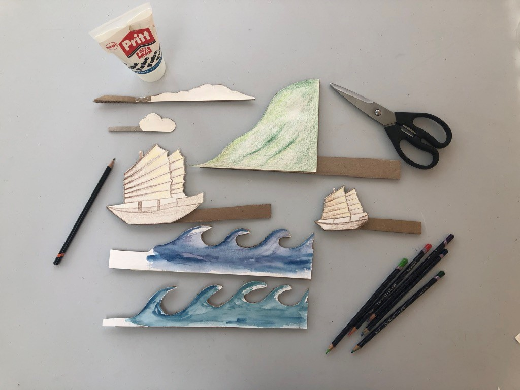Drawings of two Junk ships, a wave, clouds and a cliff with cardboard handles are on a surface. Pencils, scissors and glue are nearby.