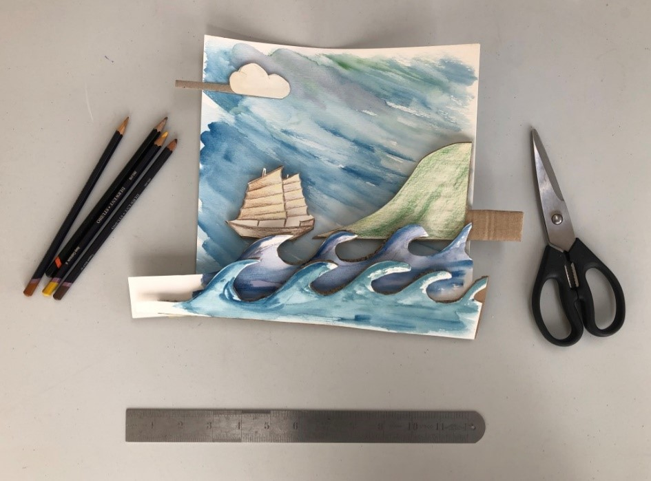 A home made craft of a ship at sea is created by painting different sections of the scene and placing one on top of the other. Pencils and scissors lie nearby