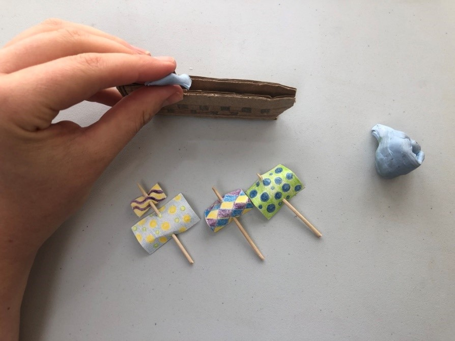 Someone puts a lump of blue tac inside a small ship made of cardboard. Three sails made of paper and toothpicks lie nearby.