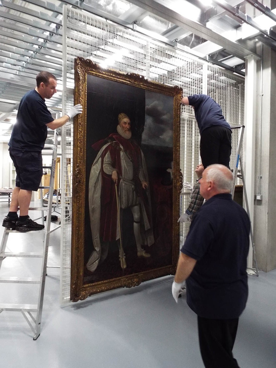 Image of Constantine technicians hanging large painting on picture racking in new PPMCC paitnings store 1