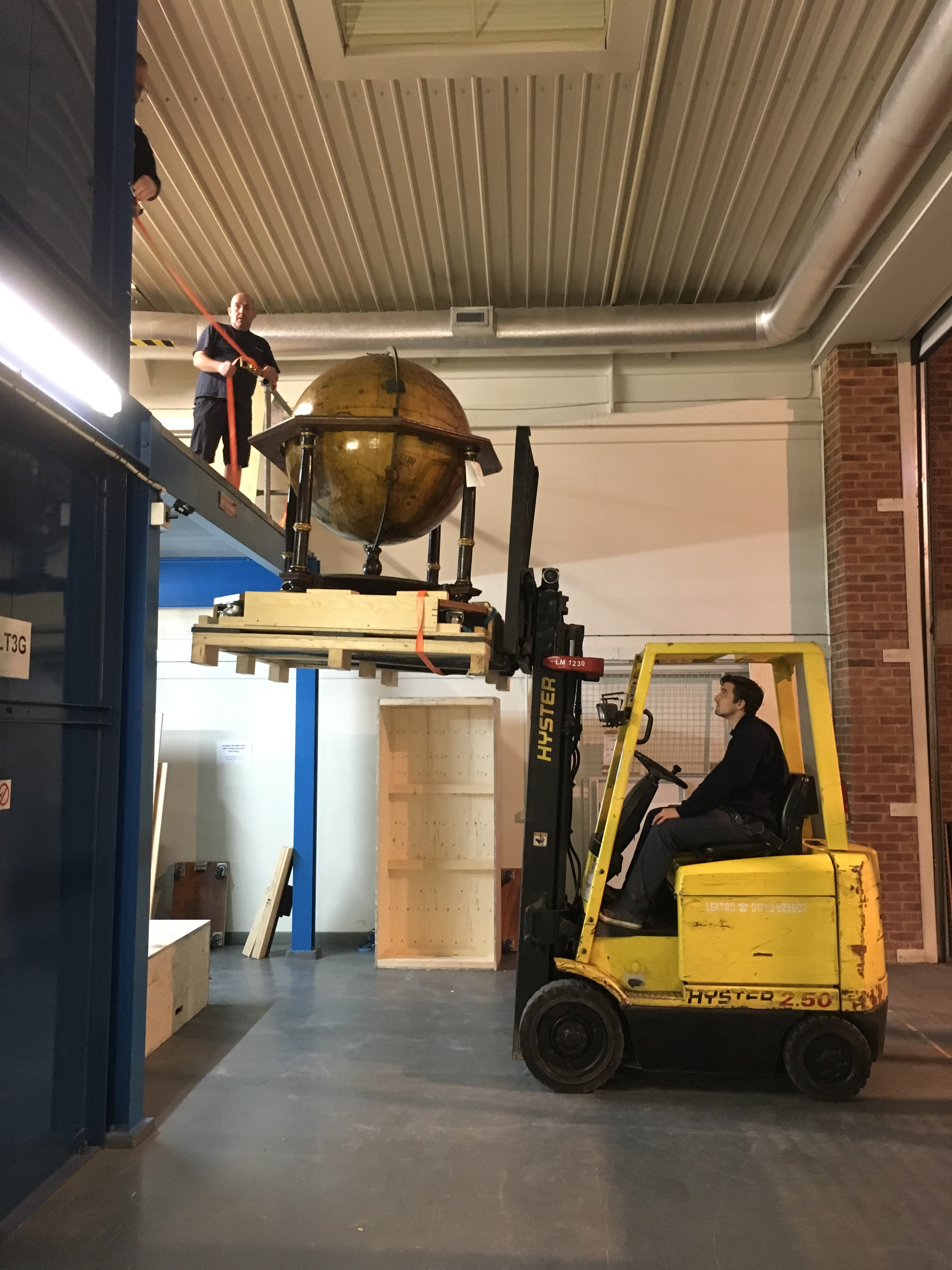Image of Constantine technicians using forklift to lower Coronelli globe from LTE mezzanine level