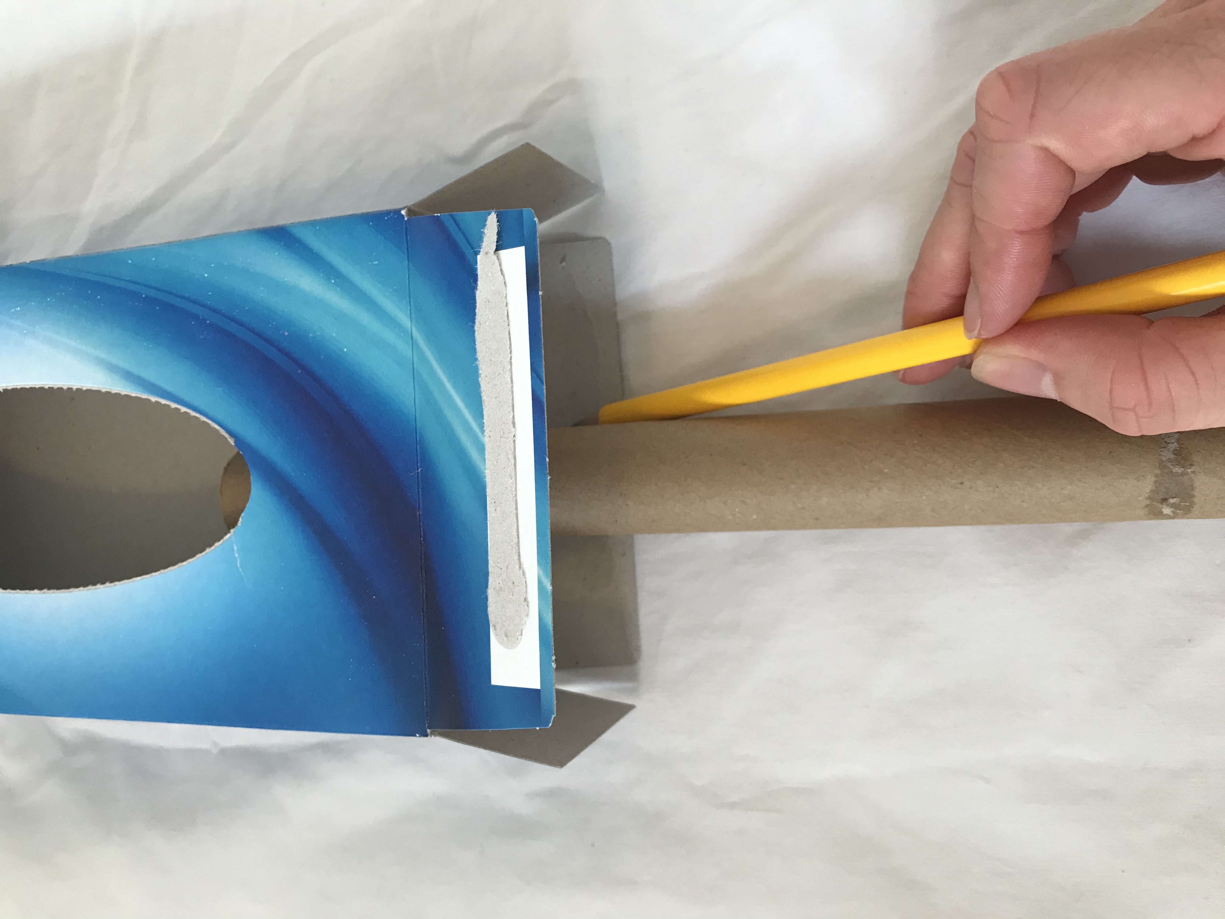 A cardboard tube is placed inside a tissue box. Someone is marking on the end of the box where the tube is.