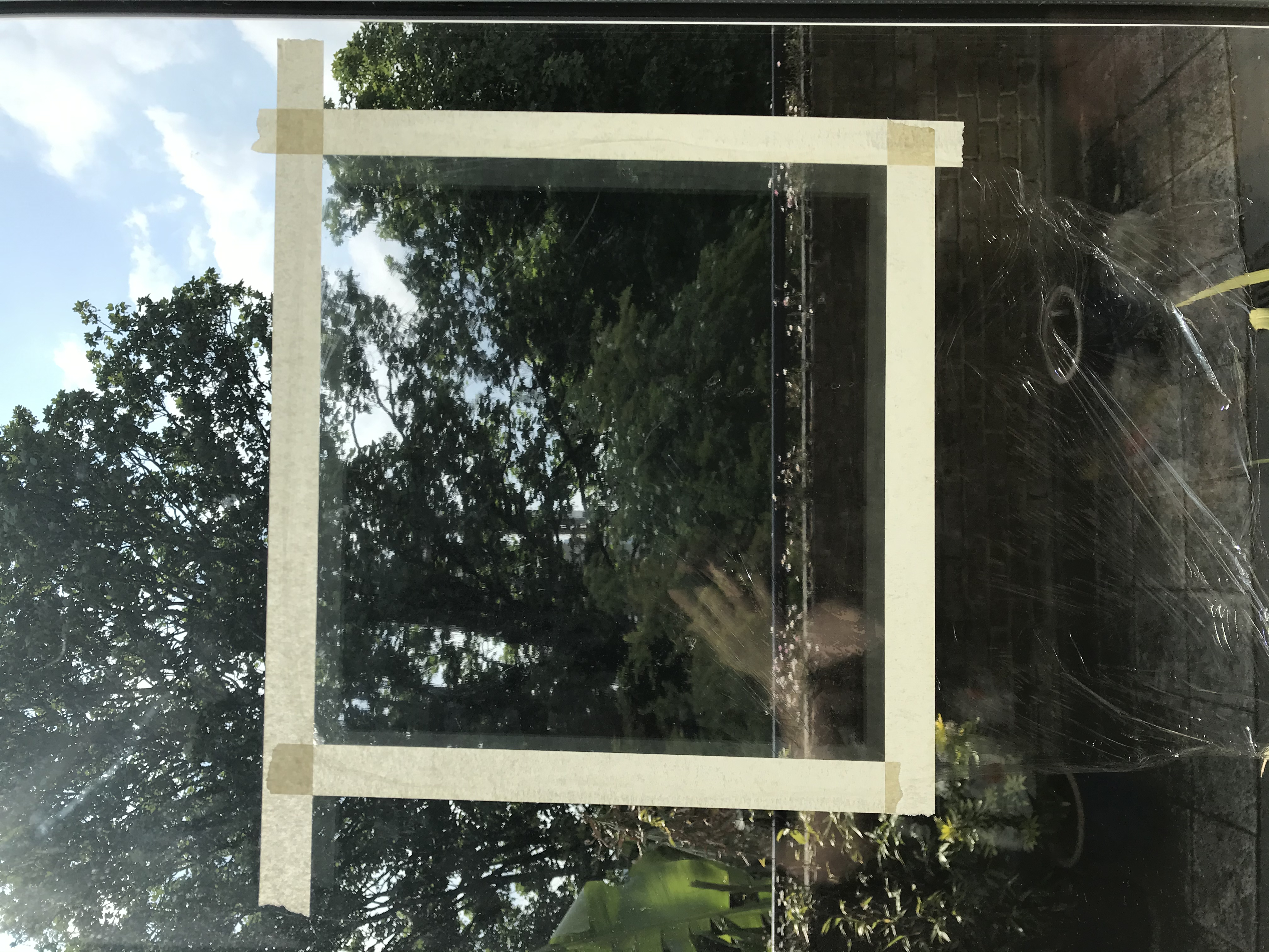Cling film has been stuck onto a window using masking tape.