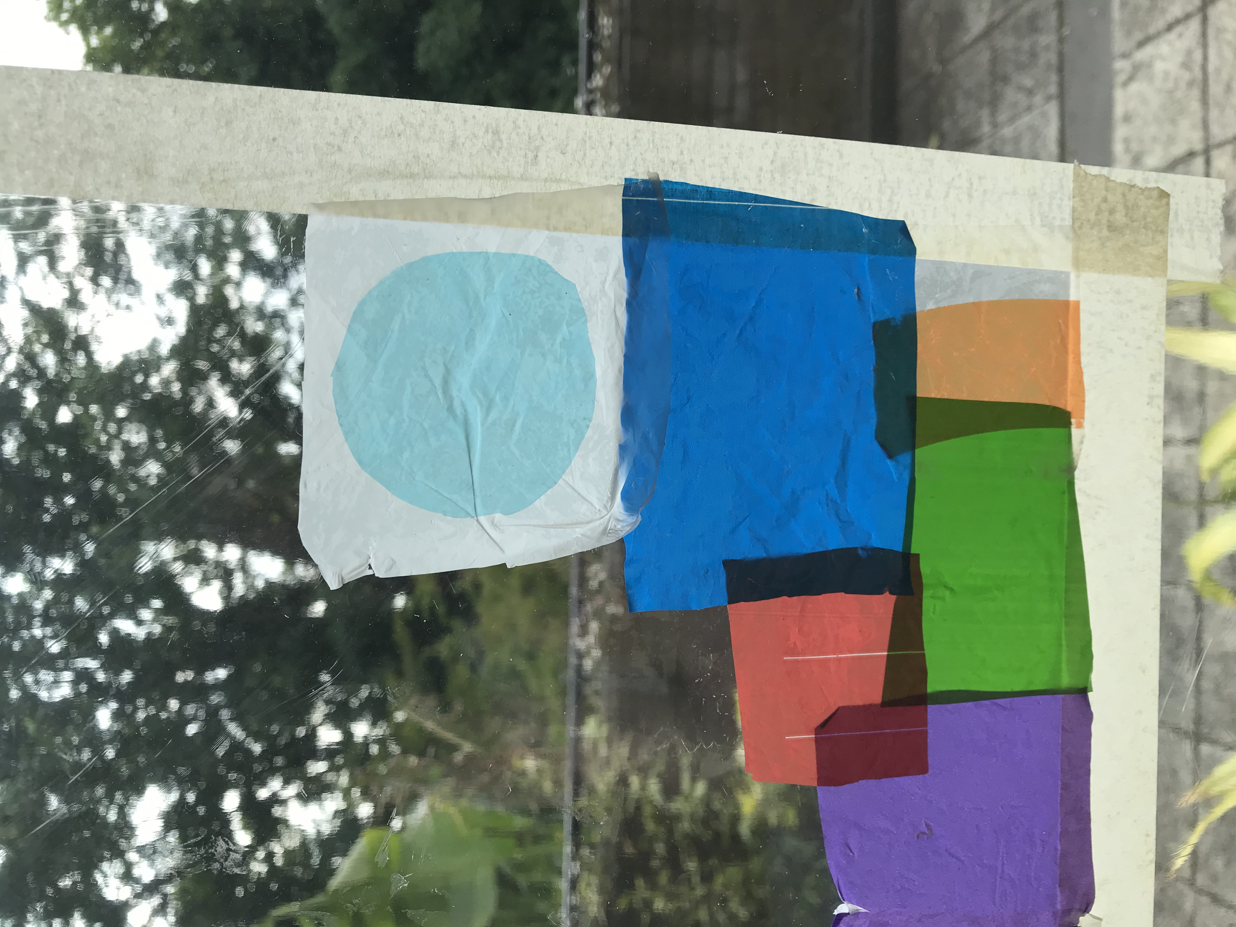 Different coloured bits of plastic bags are cut up and stuck on cling film on a window. Some colours overlap to create new colours