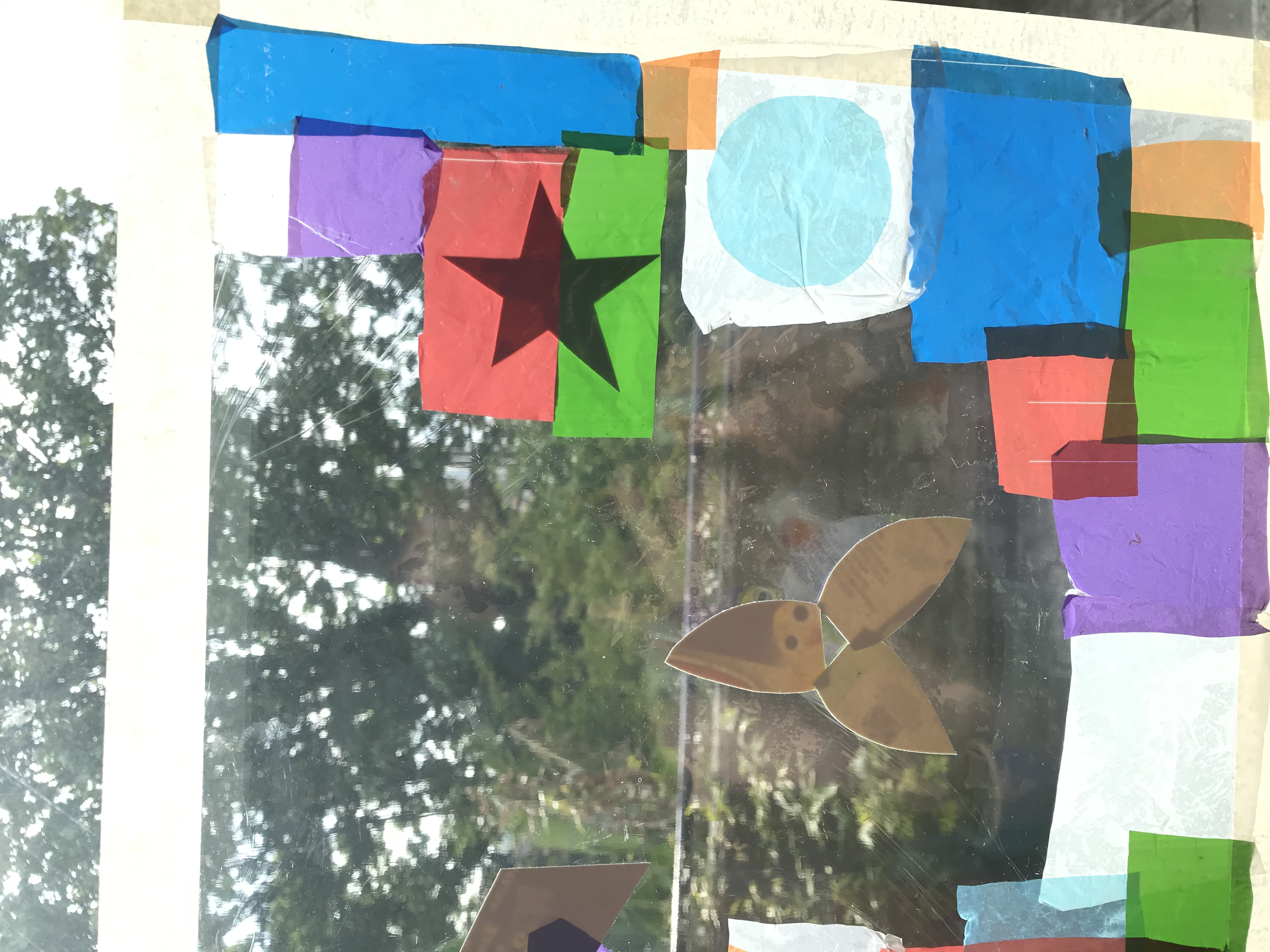 Different coloured bits of plastic bags are cut up and stuck on cling film on a window. Card has been added in a star shape to create a shadow