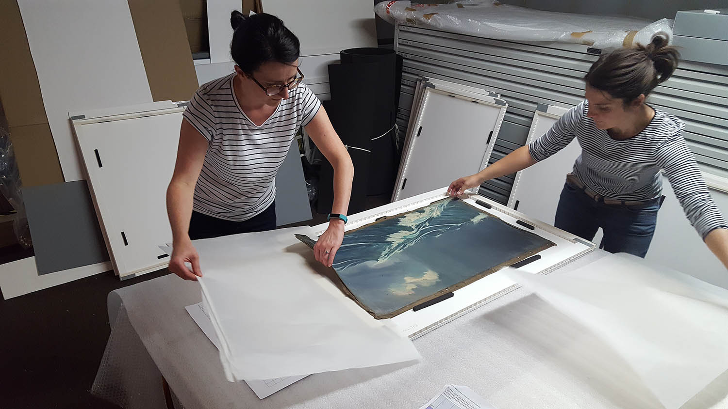 Image of Collections Storage Manager and Collections Retrieval Manager rehousing un-stretched oil paintings in custom-made trays