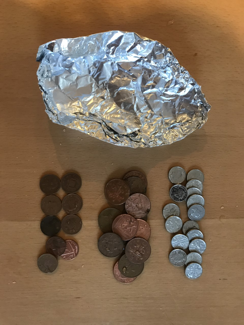 Image of tinfoil boat upside down. Next to it our three piles of coins, separated out into 1p, 2p and 5p pieces.