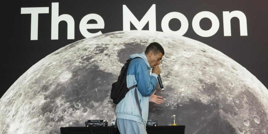 A young person is speaking into a mic in front of an image of the moon as part of the Youth Collective Late 2019