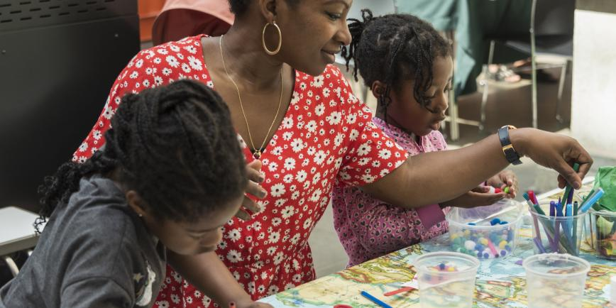 (Source of a family one lady and two children working on some art crafts Picture)