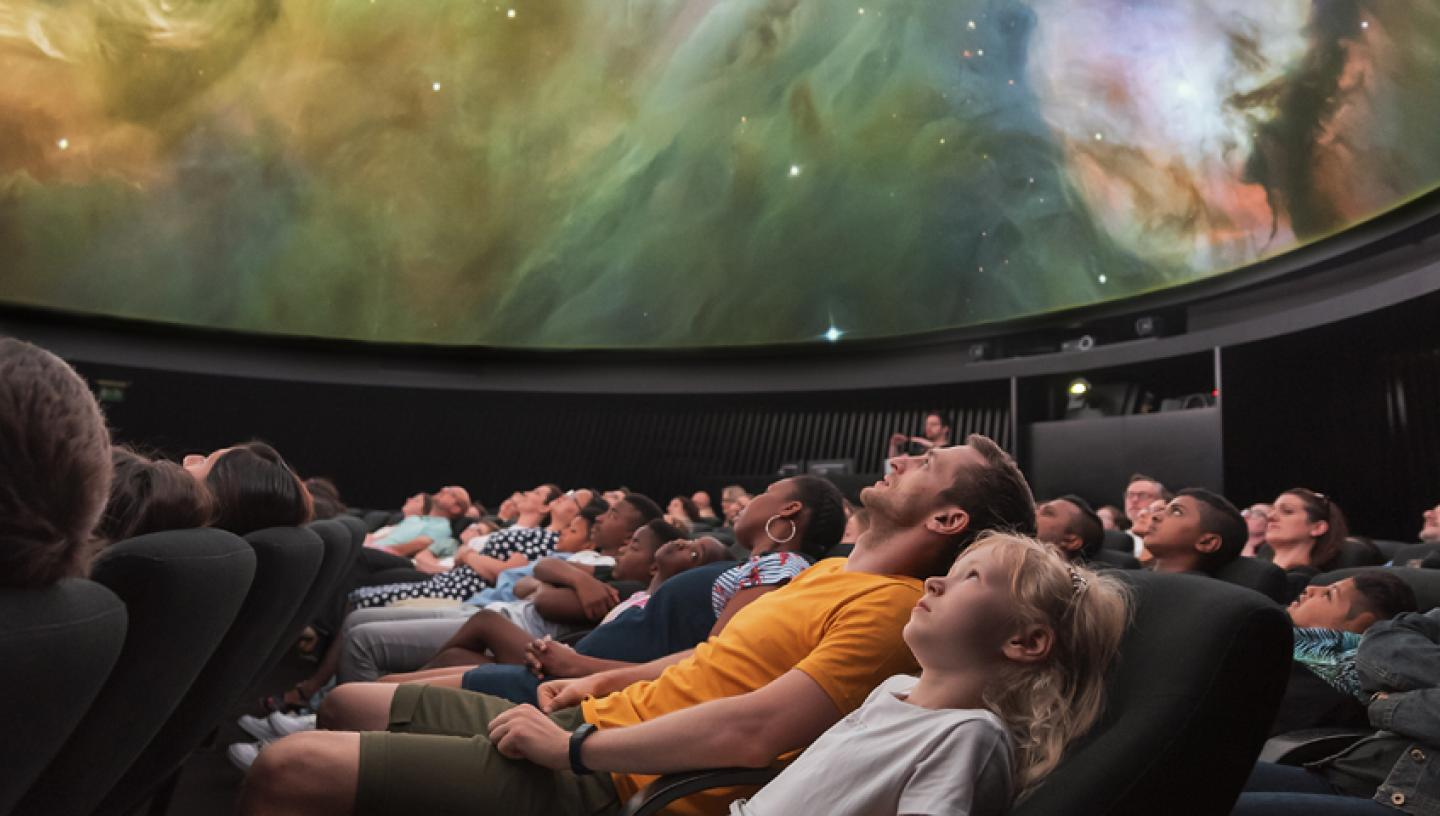 A large group of people, watching a planetarium show. The screen is showing a swirl of a galaxy