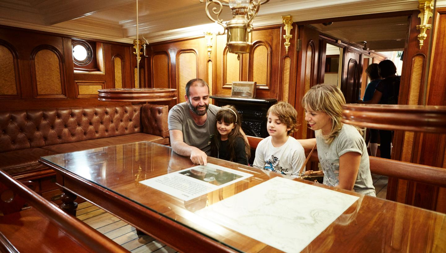 A family sits on leather padded seats inside the wood panelled captain's cabin of Cutty Sark