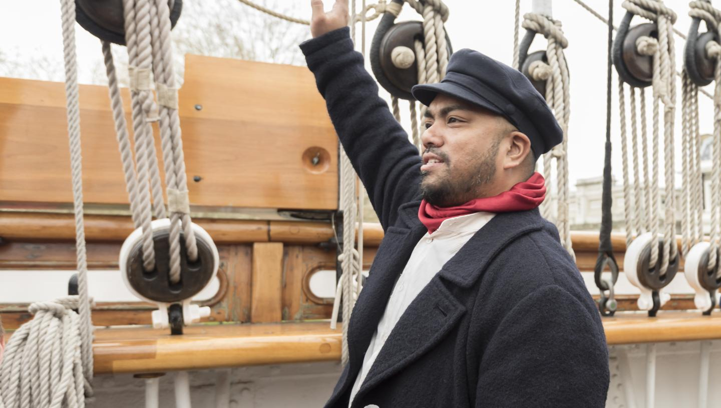 James Robson the cook, one of the characters you can meet on board Cutty Sark. He wears a flat cap and red scarf, and is pointing at the ship's rigging