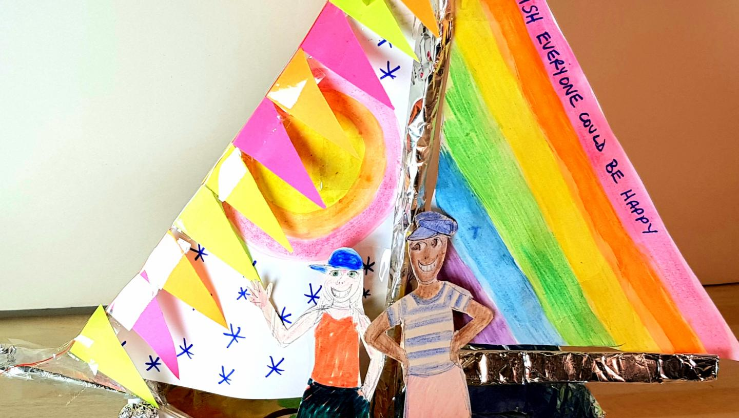 crafted boat with with rainbow sails, bunting, rainbows on the hull and two figures inside
