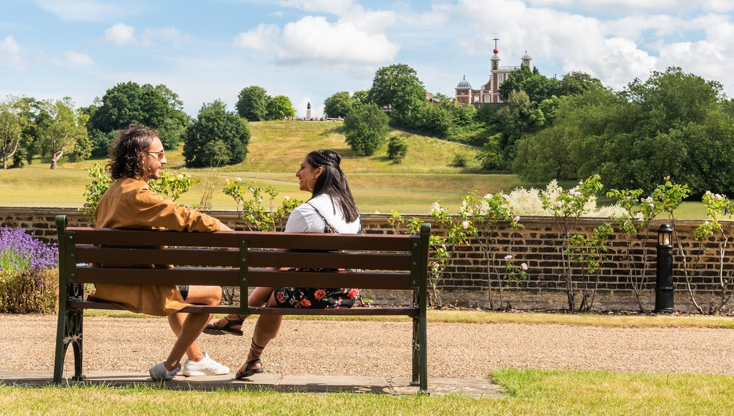 A couple sits on a bench in the sun, with Greenwich Park and the Royal Observatory in the distance