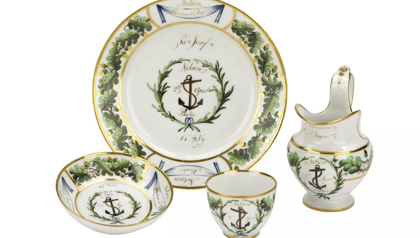 A porcelain tea set with an anchor motif and green oak leaf pattern