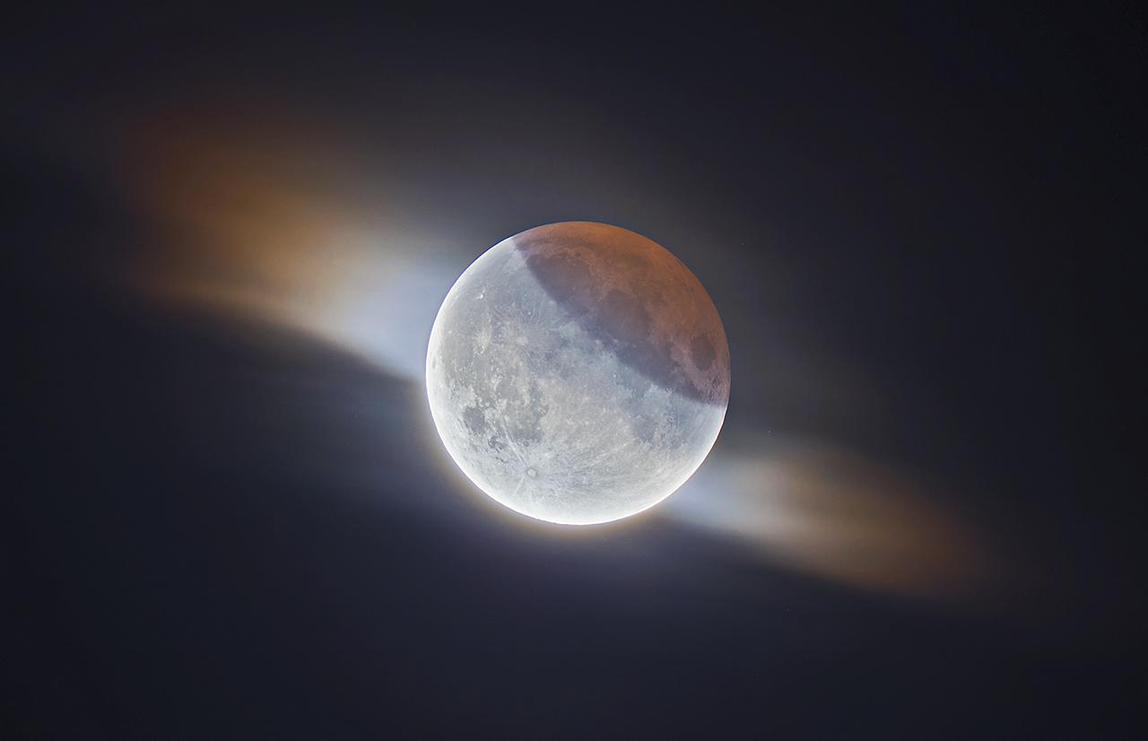 An image showing 'HDR Partial Lunar Eclipse With Clouds'
