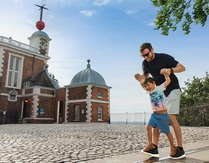 A father and son play on the Prime Meridian Line outside the historic Flamsteed House building of the Royal Observatory