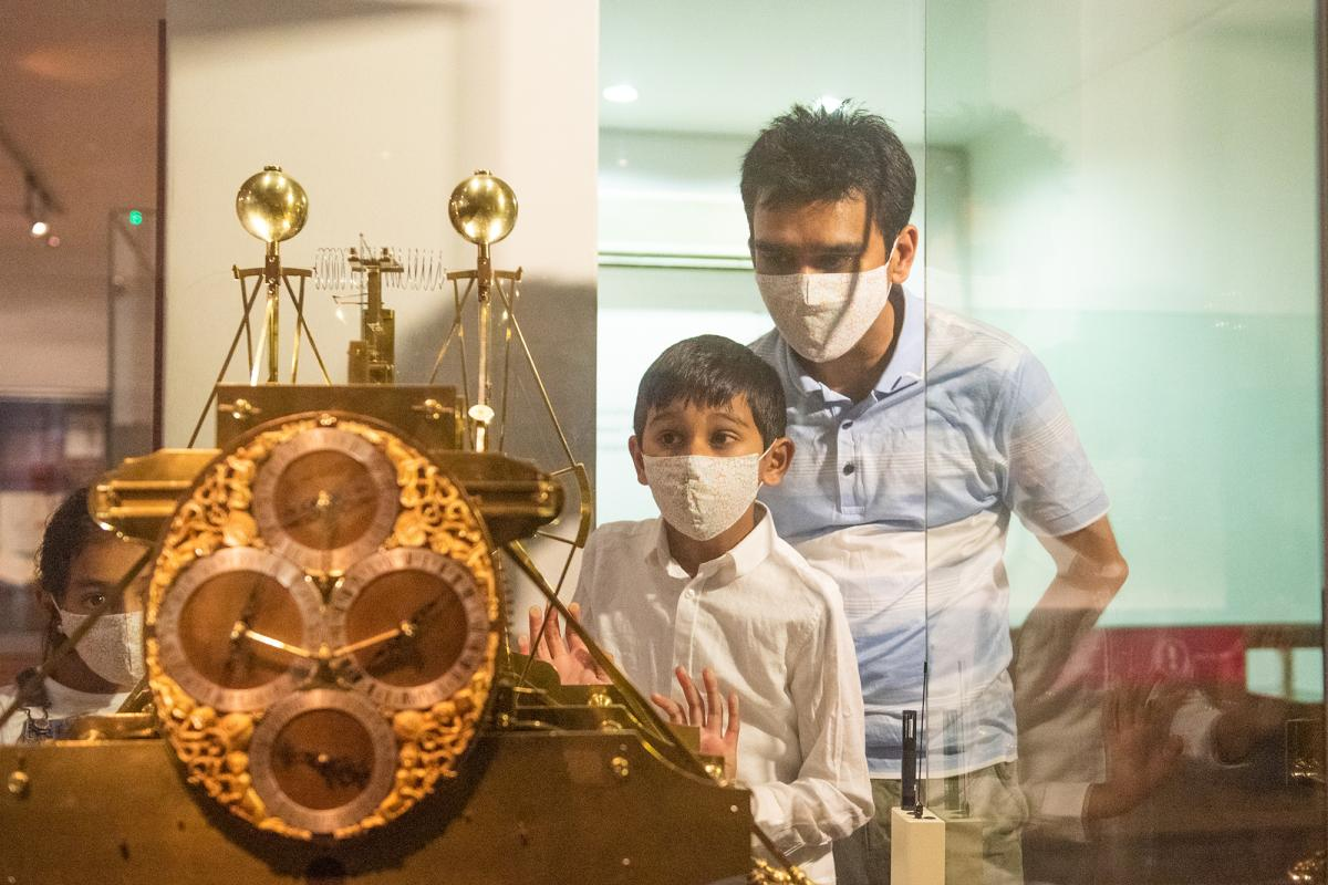 A father and son, both wearing masks, look at the display of the Harrison Clocks inside the Royal Observatory