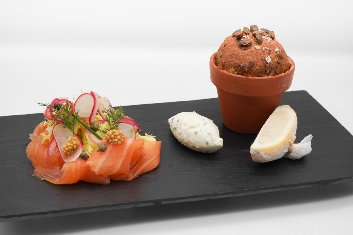 Salmon and a bread roll served on a slate plate