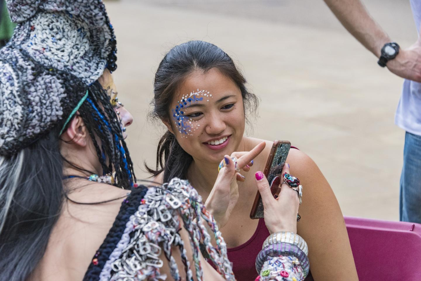 A young person with their face painted looks at an image of their face