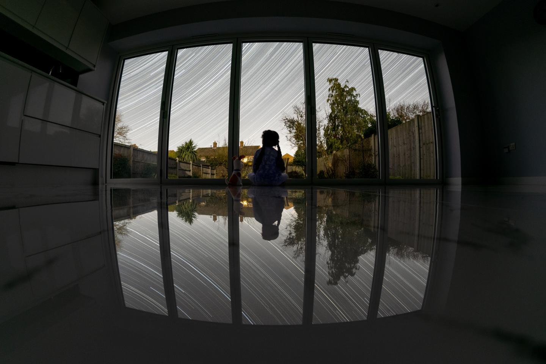 A girl sits behind bi-folding doors overlooking a garden. Star trails cross the sky above