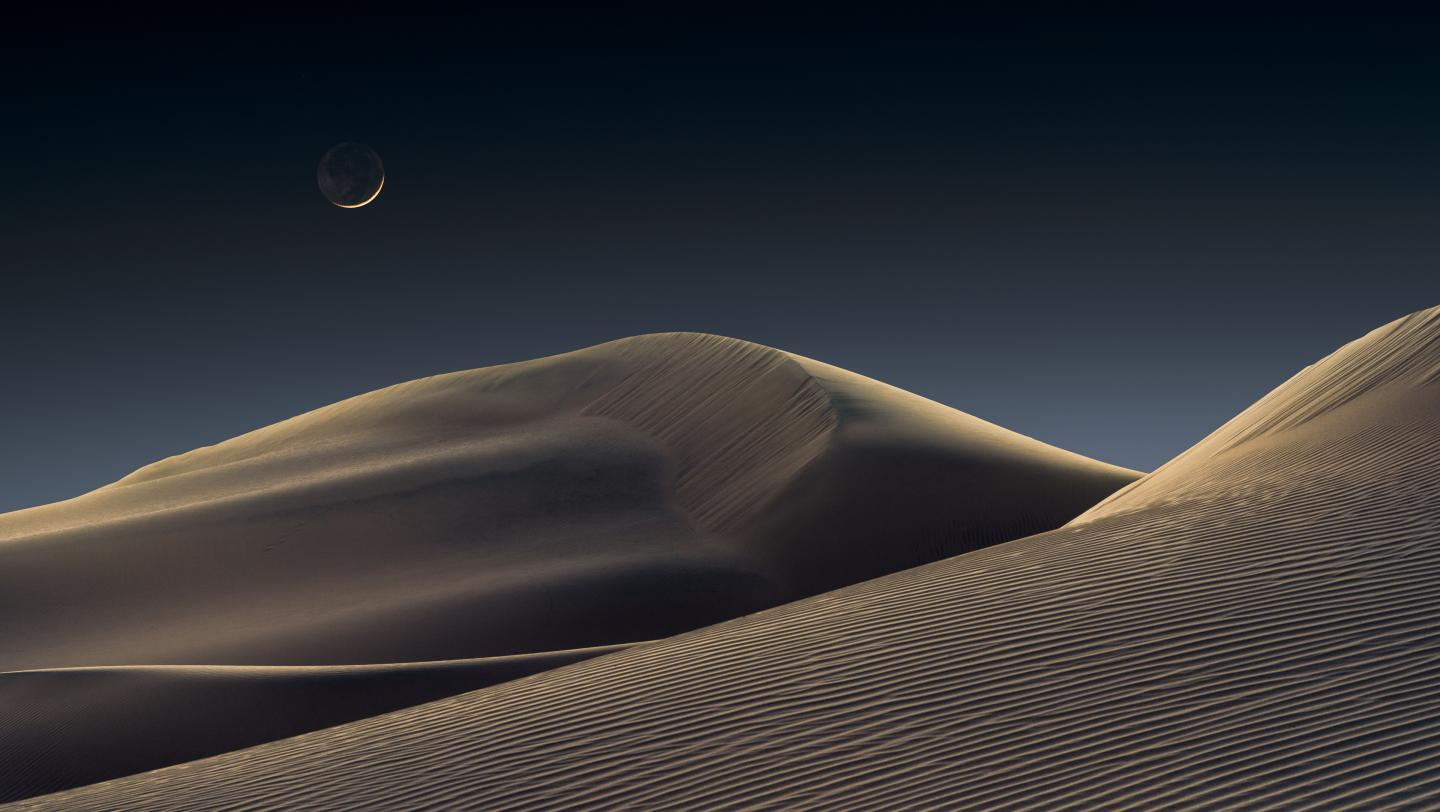 Crescent Moon rising above sand dunes