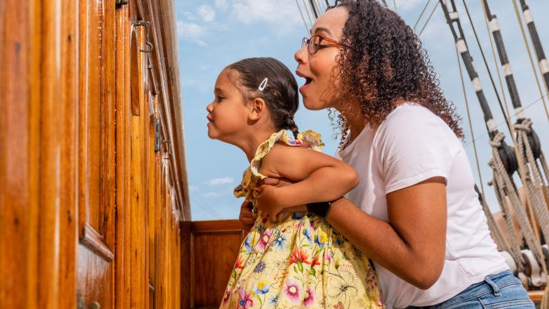 A mother and her child look in through a porthole on the main deck of Cutty Sark