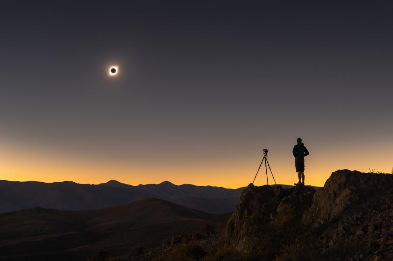 Image of person and a camera on a tripod taking a photo of the solar eclipse