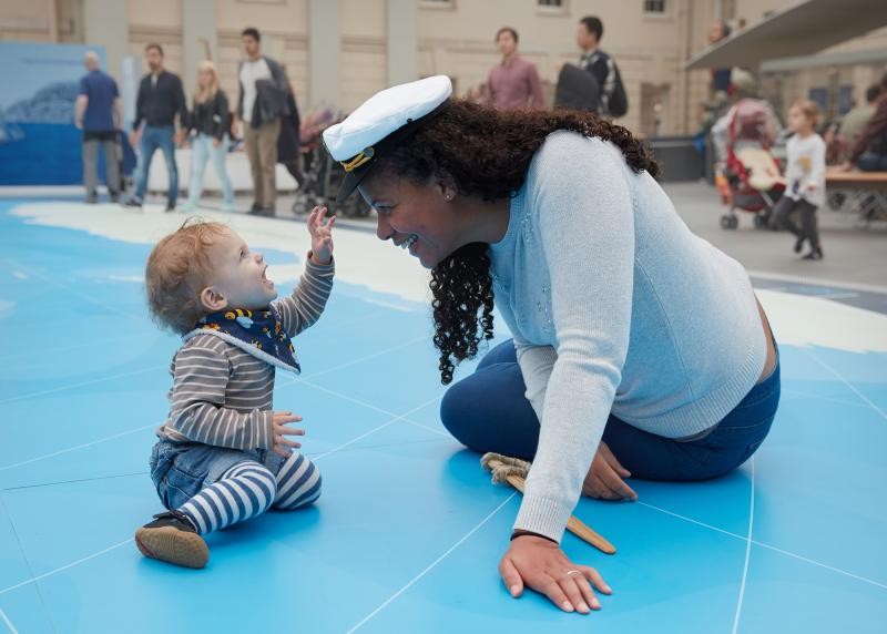 A mother and her child play on the Great Map in the National Maritime Museum. The mother has a sailor hat on