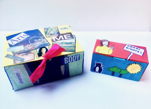 Personally decorated identity boxes, with pink ribbons, photos and words stuck on yellow cardboard boxes