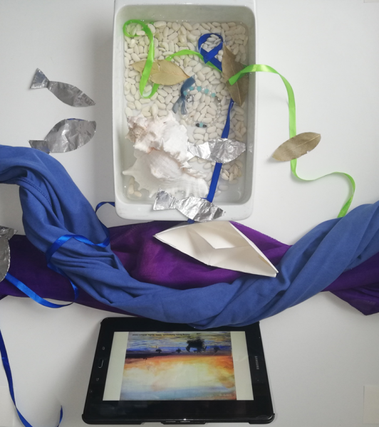 Final sensory tray showing tray filled with shells, dried beans, leaves, ribbons, foil fish on either side, blue and purple coloured fabric stretched out like a river with a paper boat and a tablet playing a video
